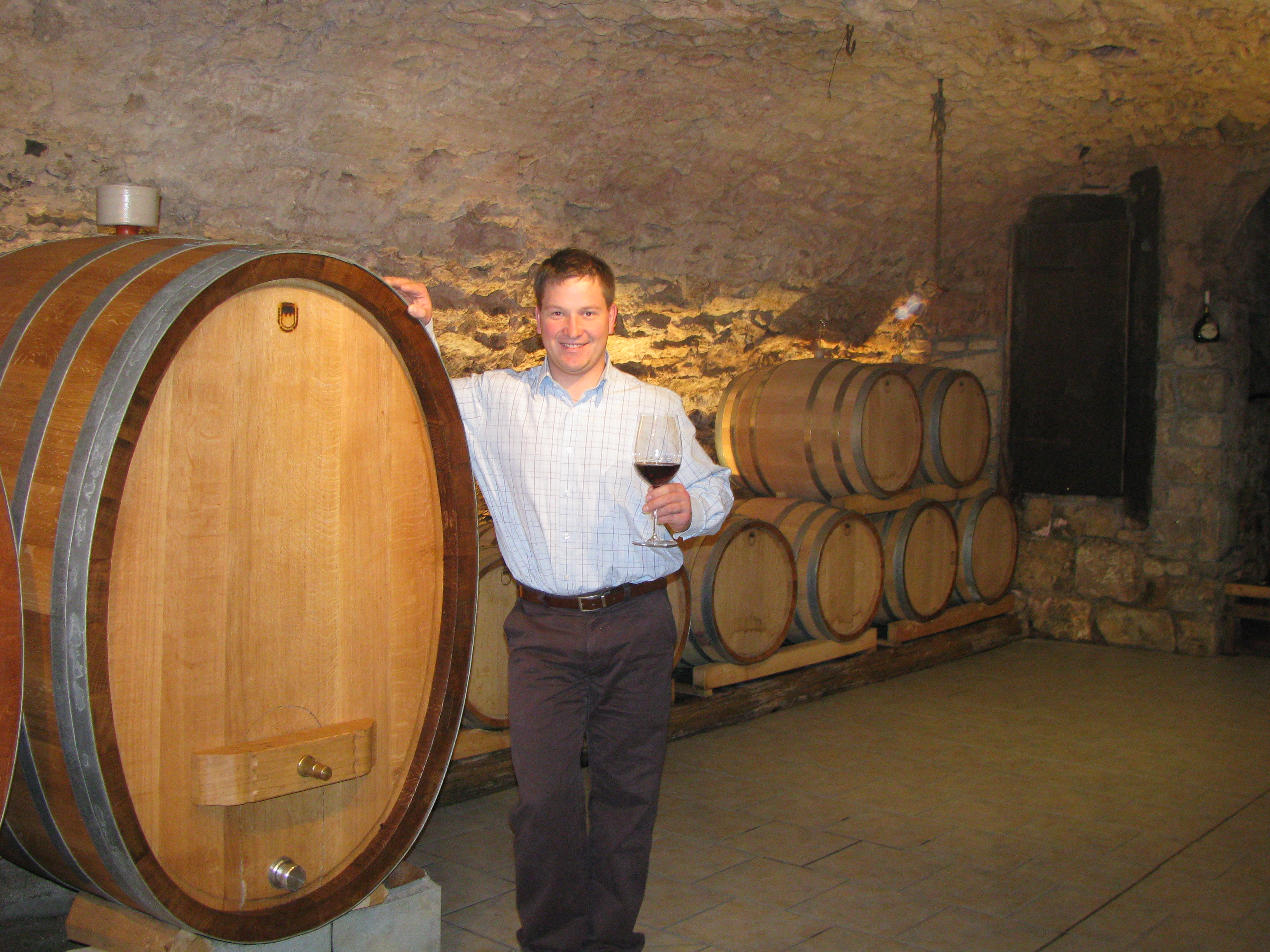 Klaus Höfling lächelnd im urigen Weinkeller. Unter anderem wird der fruchtige, trockene Qualitätswein namens Domina in Barrique-Fässern gelagert.