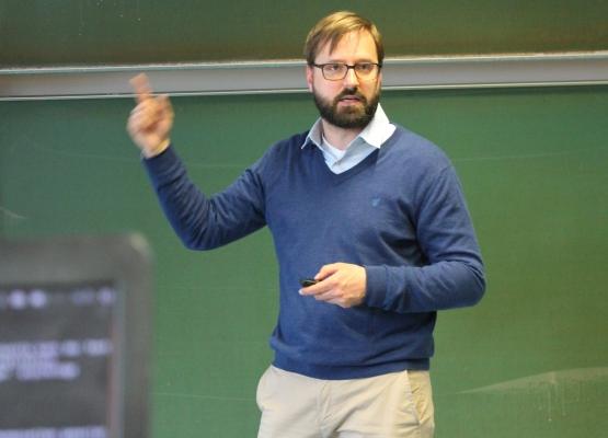 Johannes Sommer in blauem Pullover gestikuliert vor einer Tafel