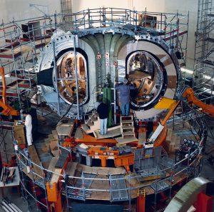 Ein Bild der Montage des Asdex Upgrade. Ein Teil der Vakuumkammer steht bereits, doch noch sind die Physiker dabei die restliche Anlage zu montieren.