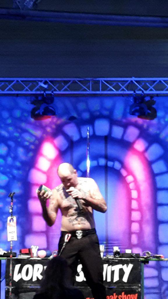 """Bizarre Szenen auf der Bühne. """"Lord Insanity"""" öffnet die Konservendose mit einem wuchtigen Schlag auf seinen Zeigefinger."""
