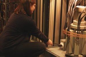 Die Frau sitzt vor dem Schrank mit dem Trommelspeicher und zieht an einem Kabel.